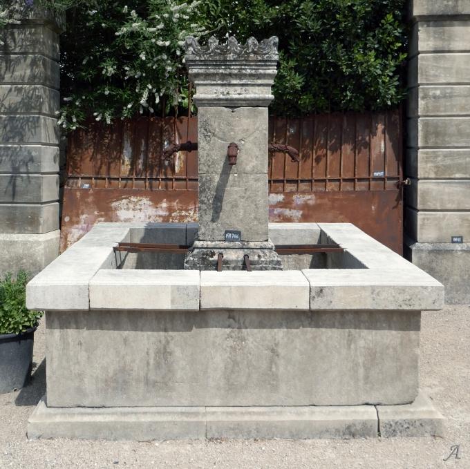 Fontaine carrée en pierre ancienne avec fût central à chapiteau crénelé - L'Isle sur la Sorgue