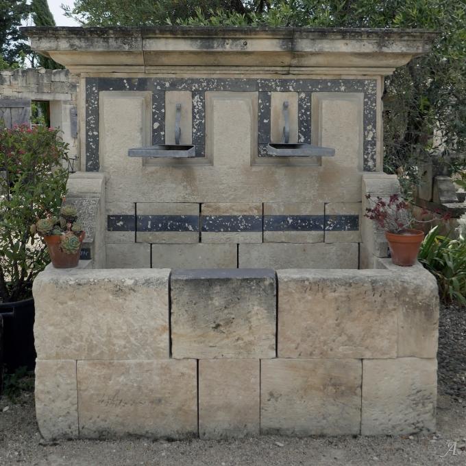 Grande fontaine murale en pierre à larges dévidoirs en métal - L'Isle sur la Sorgue